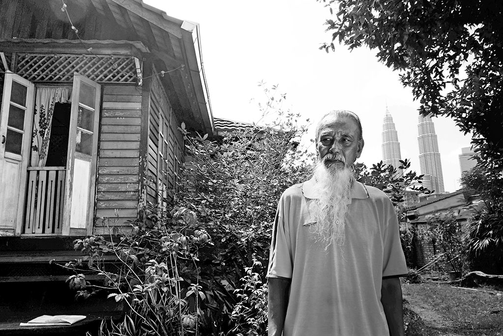 Portrait of En.Zainal in front of his house.