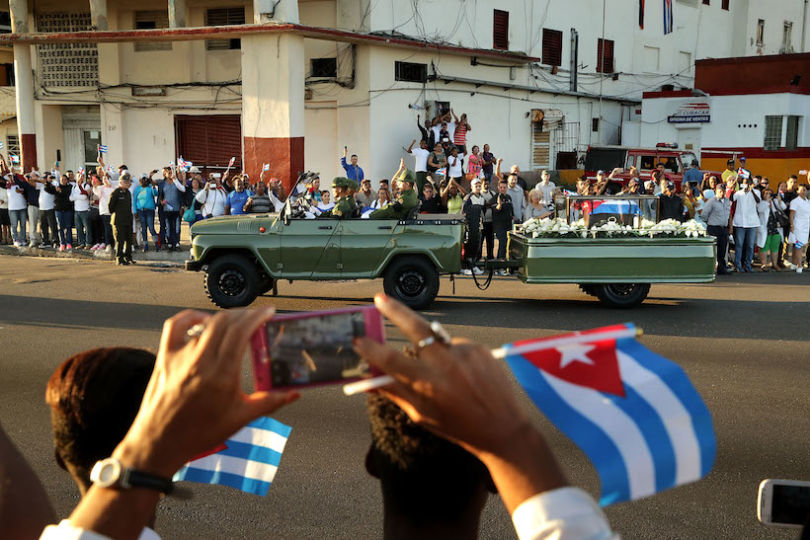 HAVANA, CUBA - NOVEMBER 30:  A military truck pulls a trailer with the flag-draped chest that holds the remains of former President Fidel Castro as thousands of Cubans line the famous Malecon seaside boulevard to pay their respects November 30, 2016 in Havana, Cuba. The revolutionary leader who brought commmunism to his island nation in 1959, Fidel Castro died November 25 at the age 90 years old.  (Photo by Chip Somodevilla/Getty Images)