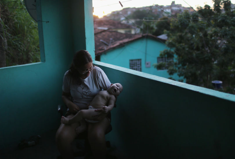 RECIFE, BRAZIL - JANUARY 25:  Mother Mylene Helena Ferreira holds her son David Henrique Ferreira, 5 months, who has microcephaly, on January 25, 2016 in Recife, Brazil. In the last four months, authorities have recorded close to 4,000 cases in Brazil in which the mosquito-borne Zika virus may have led to microcephaly in infants. Microcephaly results in newborns with abnormally small heads and is associated with various disorders including decreased brain development. According to the World Health Organization (WHO), the Zika virus outbreak is likely to further spread in South, Central and North America. At least twelve cases of Zika in the United States have now been confirmed by the CDC.  (Photo by Mario Tama/Getty Images)