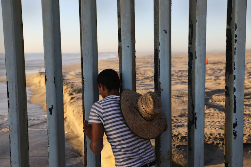 TIJUANA, MEXICO - SEPTEMBER 25: A man looks through the U.S.-Mexico border fence into the United States on September 25, 2016 in Tijuana, Mexico. Friendship Park on the border is one of the few places on the 2,000-mile border where separated families are allowed to meet. (Photo by John Moore/Getty Images)